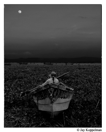 Mexican fisherman and boat at dusk in Lake Chapala, Mexico. Fine art photography.