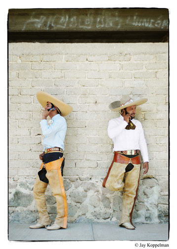 Mexican cowboys talk on cell phones outside the bull ring in Ajijic, Mexico.