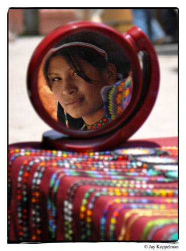 Indigenous Huichol woman reflected in mirror with bead work in Ajijic, Mexico.