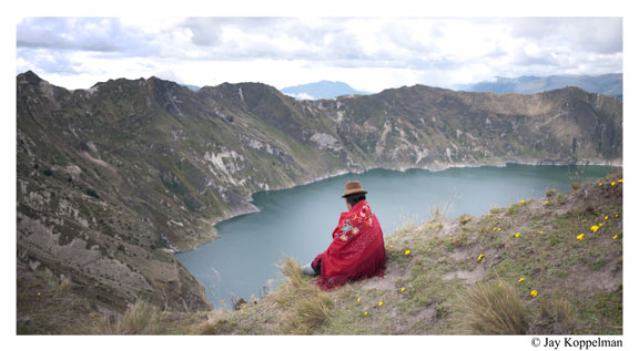 Indigenous Quechua woman sitting on the Quilotoa volcano crater in Ecuador, by Jay Koppelman.